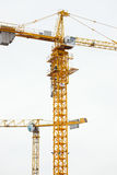 Two modern yellow construction cranes above sky Stock Photo