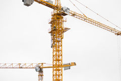 Two modern yellow construction cranes above sky Stock Photos