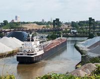 Two Modes of Transportation. A Great Lakes bulk freighter upbound on the Cuyahoga River in Cleveland, Ohio waits for a drawbridge to be raised as a coal train stock photo