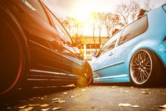 Two modified low cars in brown and light blue color. Stance custom cars with a forged polished wheels parked on a street at sunny. Day. Tuned automobiles alloy royalty free stock images