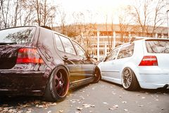 Two modified low cars in brown and light blue color. Stance custom cars with a forged polished wheels parked on a street at sunny. Day. Tuned automobiles with royalty free stock photo