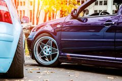 Two modified low cars in purple candy and light blue color. Stance custom cars with a forged polished wheels parked on a street at. Sunny day. Tuned automobiles royalty free stock photography
