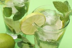Two mojito cocktails on green background Stock Image