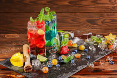 Two mojitos on a wooden background. Cocktails with berries, mint and ice. Alcoholic blue mojito. Delicious red mojito. Copy space. Royalty Free Stock Images