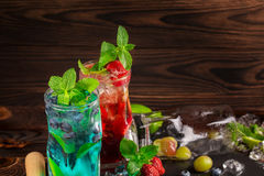 Two mojitos on a wooden background. Cocktails with berries, mint and ice. Alcoholic blue mojito. Delicious red mojito. Copy space. Royalty Free Stock Image