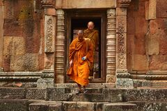 Two Monk in Orange Robe Walking Down the Concrete Stairs Royalty Free Stock Image