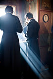 Two monks eat after the Liturgy. Two monk eat after the Liturgy near the window full of light. Orthodox liturgy with bishop Mercury in High Monastery of St Peter Stock Image