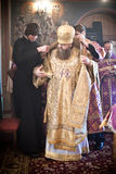 Two monks help the Bishop to robe. Orthodox liturgy with bishop Mercury in High Monastery of St Peter in Moscow on March 14, 2010 in Moscow Stock Photo