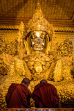 Two monks praying by the golden Buddha statue, Myanmar (Burma) Stock Photo