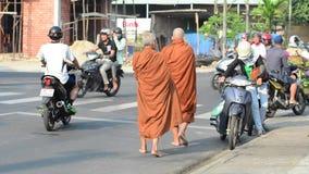 Two monks seeking alms on a street in Hanoi stock footage