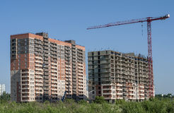Two monolith-brick buildings and a crane Royalty Free Stock Photos