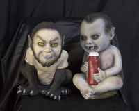 Two monster babies one drinking a bottle full of blood Stock Photo