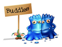 Two monster friends near a signboard Royalty Free Stock Photos
