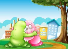 Two monsters at the hilltop hugging each other near the tree Stock Image
