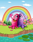 Two monsters at the riverbank with a rainbow in the sky. Illustration of the two monsters at the riverbank with a rainbow in the sky Royalty Free Stock Image
