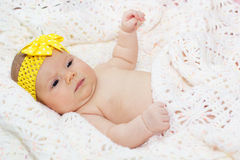 Two month baby girl with yellow ribbon on head Stock Photo