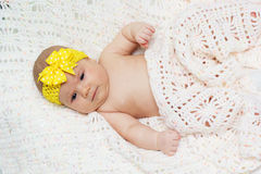 Two month baby girl with yellow ribbon Royalty Free Stock Photography