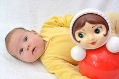 The two-month baby lies near a doll tumbler toy on a white background Royalty Free Stock Photo