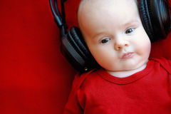 Two month old baby with earphones Royalty Free Stock Images