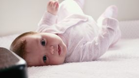 Baby lie on stomach. A two-month-old child lies on a bed and rolls from stomach to back stock video
