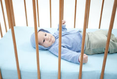 Two months baby boy lying in a crib Royalty Free Stock Images