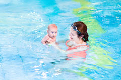 Two months old baby boy and his mother swimming. Cute two months old baby boy and his attractive young mother enjoying swimming stock image