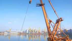 Two moored floating cranes stand in the port in anticipation of a tugboat. 4K. Two moored floating cranes stand in the port in anticipation of unloading the stock video footage