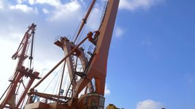 Two moored floating cranes stand in the port in anticipation of a tugboat. 4K. Two moored floating cranes stand in the port in anticipation of unloading the stock footage