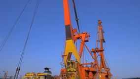 Two moored floating cranes stand in the port in anticipation of a tugboat. 4K. Two moored floating cranes stand in the port in anticipation of unloading the stock video