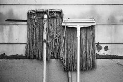 Two Mop old resting against the wall. Stock Photography
