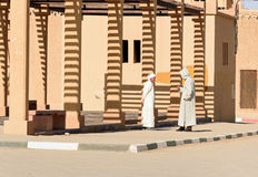 Two Moroccan men in white djellaba talk on the street in Merzouga village, Morocco Stock Photos