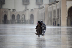 Two Moroccans run through the rain Stock Image