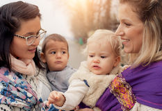 Two mothers with babies in baby carriers warp royalty free stock images