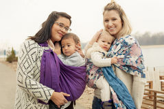 Two mothers with babies in baby carriers warp Stock Images
