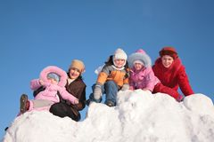 Two mothers with child on snow hill Royalty Free Stock Photo