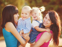 Two mothers with children in summer park Stock Photo