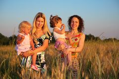Two mothers with children on wheaten field Stock Photography