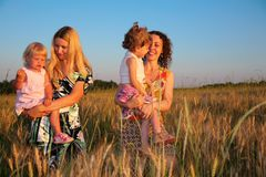Two mothers with children on wheaten field Stock Photos