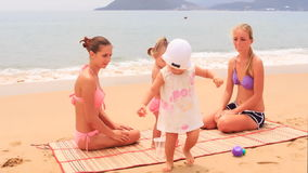 Two mothers little daughters sit on mat and play stock video