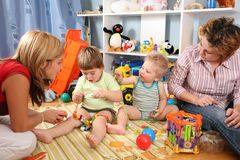 Two mothers play with children in playroom 2 Stock Photos