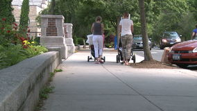Two mothers pushing strollers down sidewalk. A view or scene from around town stock footage