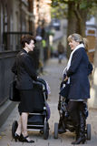 Two mothers pushing their strollers, talking Stock Photos