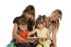 Two mothers read books to their children Royalty Free Stock Images