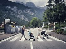 Two mothers with strollers crossing the road. the photo was taken in Molveno, Italy. Beatles style. Abby road style.  Royalty Free Stock Photo