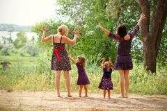 Two mothers with their daughters on the field in summer Stock Image
