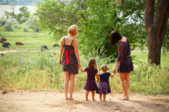 Two mothers with their daughters on a summer field, rear view Royalty Free Stock Photo