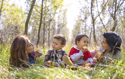 Two mothers with their kids eating apples Stock Image