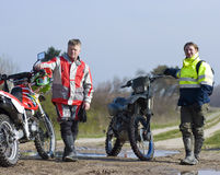 Two motocross riders. Proudly presenting their motorbikes royalty free stock photo