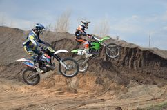 Two motocross riders on a motorbike jumps. Over the earthen pit Stock Photo