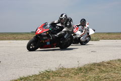 Two motorbike racers in the left turn on the track. Royalty Free Stock Photo